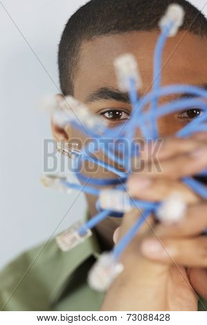 Young man holding Ethernet cables