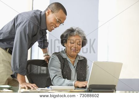 Man leaning over desk of mature woman with computer