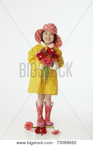 Girl in raincoat holding flowers