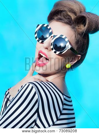 Colorful portrait of young attractive laughing woman wearing stripy sunglasses