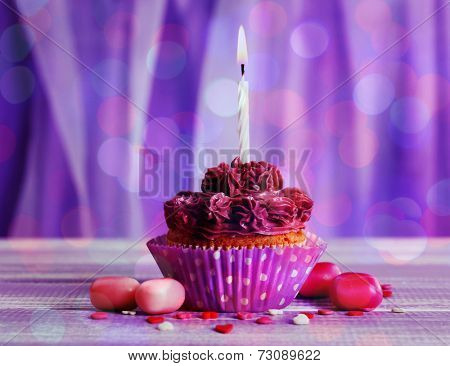 Tasty cupcake on bright purple background