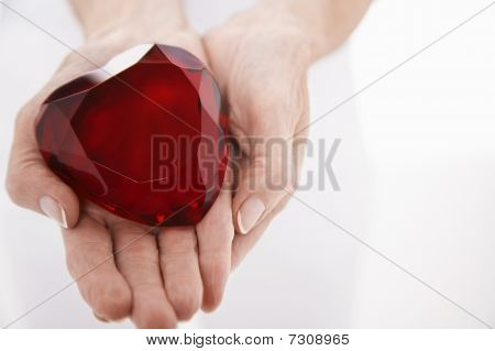 Woman showing heart-shaped jewel close up on hands