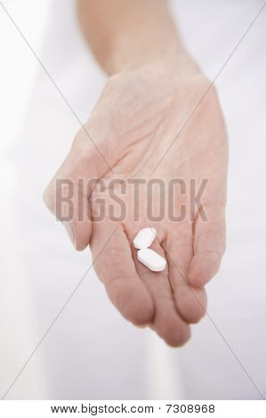 Senior Woman holding Pillen in der hand close up auf Seite
