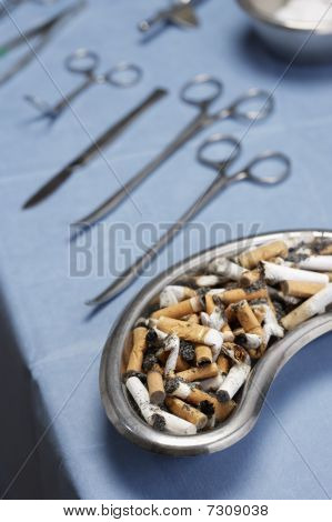 Cigarettes in medical tray with operating equipment on table