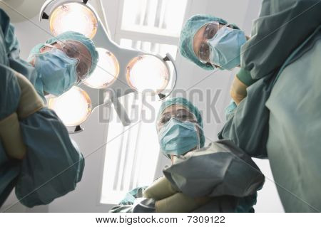 Surgeons in operating theatre looking down at patient personal perspective