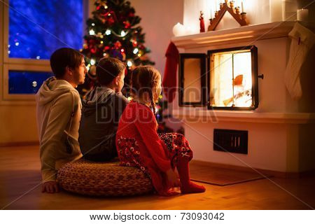 Father and his two little kids sitting by a fireplace in their family home on Christmas eve