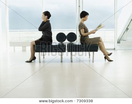 Businesswomen Sitting on Benches facing opposite directions talking on mobile reading newspaper prof