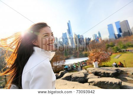 Woman in Central park, New York City in late fall early winter with skating rink in background. Candid smiling multi-ethnic girl on Manhattan, USA.