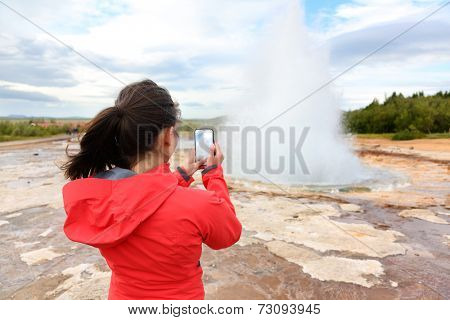 Iceland tourist taking photos of geyser Strokkur. Woman visiting famous tourist attractions and landmarks on the Golden Circle. Girl on holiday vacation sightseeing Icelandic nature.