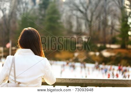 Central park skating rink - woman in New York City in late fall early winter with skating rink in background. Candid smiling multi-ethnic girl on Manhattan, USA.