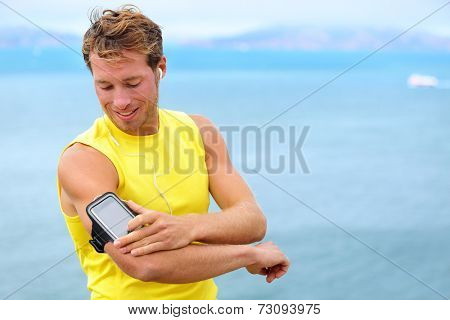 Running training music on smartphone app. Runner man listening to music adjusting settings on armband for smart phone. Fit male fitness model working outdoor by water.