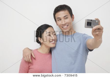 Young man arm around girlfriend taking picture of themselves