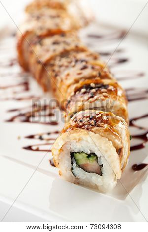 Roll made of Fresh Salmon, Smoked Eel, Cream Cheese and Cucumber inside. Topped with Smoked Eel