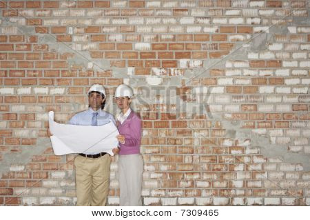 Construction manager and architect examining plans