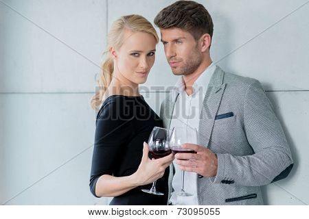 Young couple enjoying a romantic evening together in stylish evening wear drinking red wine with the beautiful blond woman looking at the camera