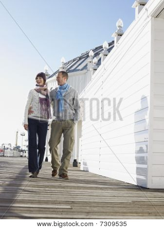 Embracing couple walking along pier