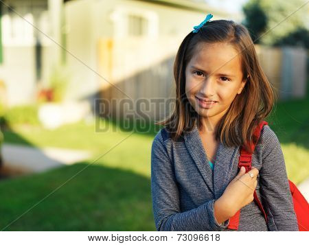 little schoolgirl with backpack outside ready to go to school