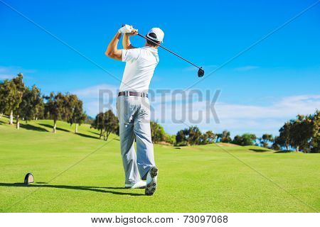 Golf player teeing off. Man hitting golf ball from tee box with driver.