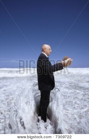 Senior business man reading newspaper standing in ocean wave side view