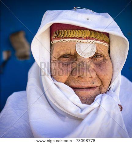Portrait of very elderly woman wearing golden jewelry under head scarf closeup