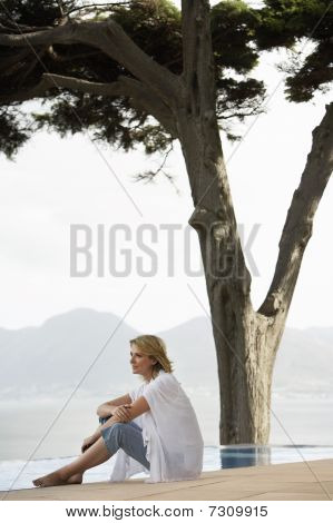 Woman sitting by infinity pool side view