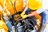 stock photo of machinery  - Asian motor mechanic working on construction or mining machinery in vehicle workshop - JPG