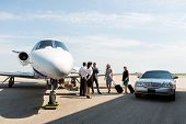 image of jet  - Business people with pilot and airhostess standing near private jet and limo at terminal - JPG
