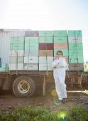 pic of bee keeping  - Portrait of female beekeeper with arms crossed standing against truck loaded with honeycomb crates - JPG