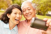 stock photo of two women taking cell phone  - Senior Asian Couple Taking Selfie In Park Together - JPG