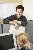 picture of partition  - Businessman talking to colleague over cubicle wall - JPG