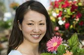 Woman Holding Flowers In Plant Nursery, Portrait, Close Up