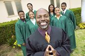 image of minister  - Minister in church garden gospel choir in background portrait - JPG