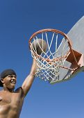 Young man dunking basketball into hoop (action shot)