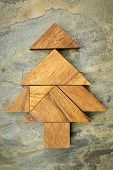 stock photo of tangram  - abstract picture of a Christmas tree built from seven tangram wooden pieces over a slate rock background - JPG