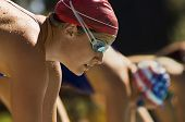 Female swimmers on starting blocks (side view)