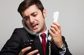 stock photo of stress  - Stressed businessman talking on many phones at once - JPG