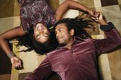stock photo of adoration  - African American couple laying on floor holding hands - JPG