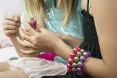 Young girl applying nail polish to friends fingernails close-up poster