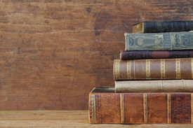 stock photo of leather-bound  - old books on wooden shelf - JPG