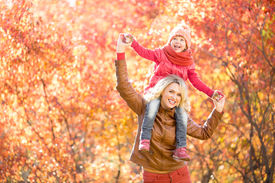 stock photo of red-necked  - Happy parent and kid walking together outdoor in autumn park - JPG