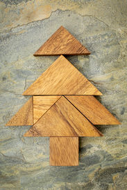 pic of tangram  - abstract picture of a Christmas tree built from seven tangram wooden pieces over a slate rock background - JPG