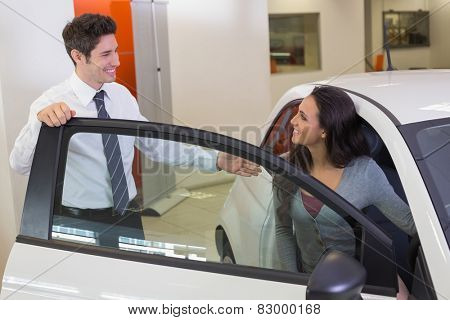 Salesperson speaking with happy client at new car showroom