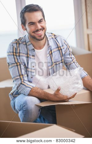 Smiling man unpacking cardboard boxes in his new home