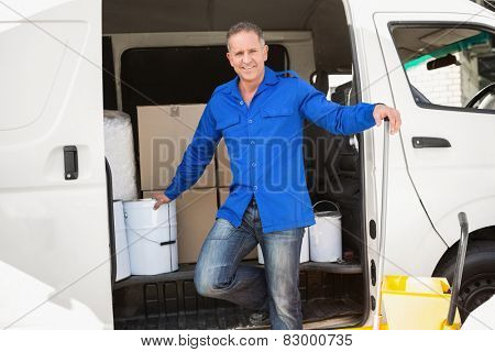 Cleaning agent smiling at camera in front of his van