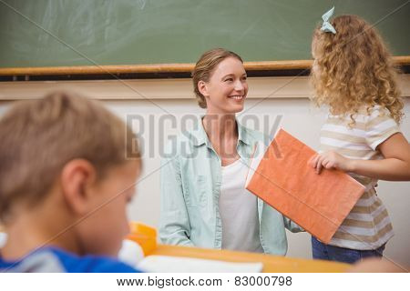 Cute pupil looking her teacher during class presentation at the elementary school