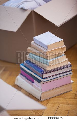 Pile of books on the floor in a new home