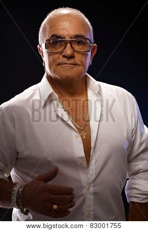 Portrait of old playboy in white shirt and lots of gold jewels.