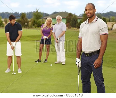 Young black man smiling happy on golf course, holding golf club.