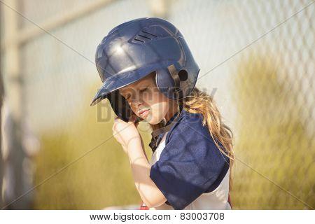 Girl Putting on a baseball Helmut