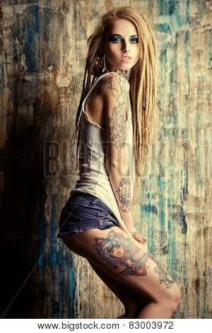Modern girl with blonde dreadlocks. Jeans style. Modern generation.